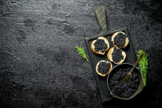 ボウルに黒キャビア、ディル付きまな板にキャビアを挟みます。黒の素朴な表面に