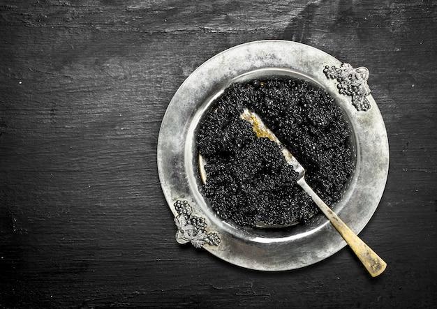Черная икра в миске. на черной доске.