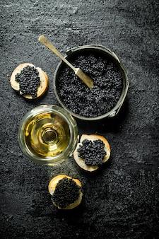 Черная икра в миске с бутербродами и вином. на черном деревенском фоне