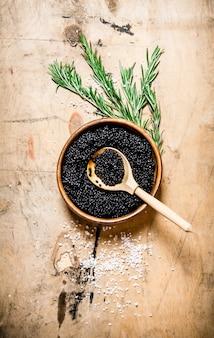 ローズマリーと塩の入ったカップに入った黒キャビア。木製のテーブルの上。上面図