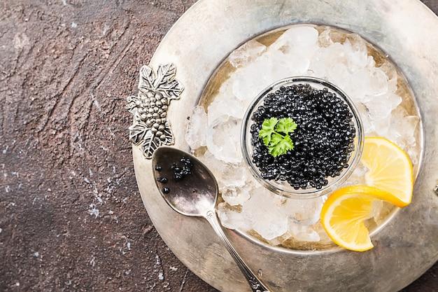 レモンと氷の上のガラスのボウルの黒いキャビアは、暗い表面の上面図の上にクローズアップ