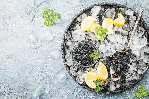 レモンと氷の上のガラスのボウルの黒いキャビアは灰色の表面の上面図の上にクローズアップ