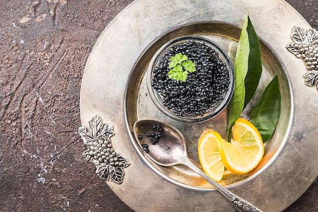 レモンとガラスのボウルの黒いキャビアは、暗い表面の上面図の上にクローズアップ