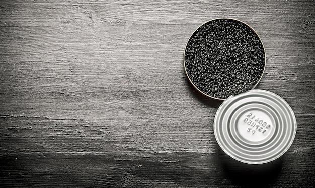 瓶の中の黒いキャビア。黒い木製のテーブルの上。テキスト用の空き容量。上面図