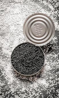 塩入りの瓶に入った黒キャビア。黒い木製のテーブルの上。上面図