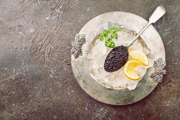 レモンと氷の上のスプーンで黒いキャビアは暗い表面の上面図の上にクローズアップ