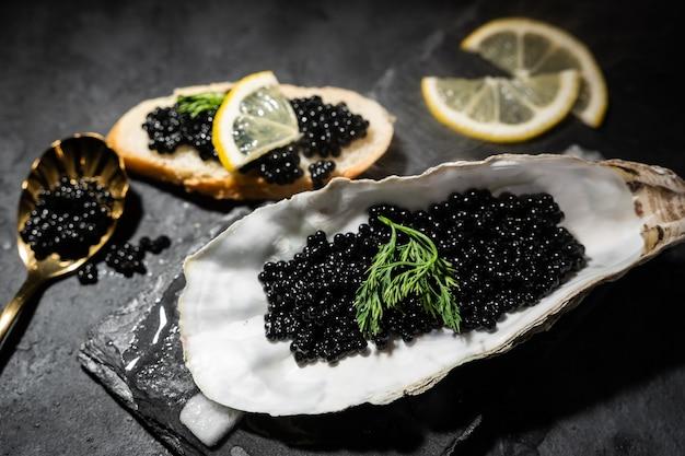 Черная икра в раковине устрицы на фоне черного сланца