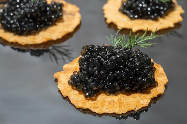 暗い背景のタルトの黒いキャビア。健康食品のコンセプト。スペースをコピーします。