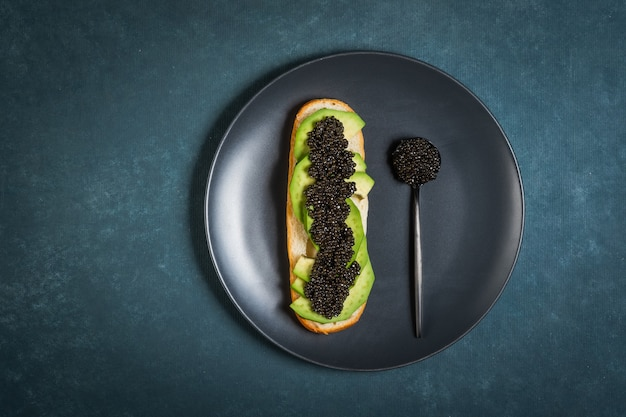 クリームチーズとビスケットのチョウザメの黒キャビア。キャビアをスプーンで。丸い青いプレート。暗い表面