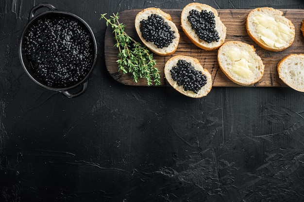 Black caviar served on baguette, on black table, top view flat lay