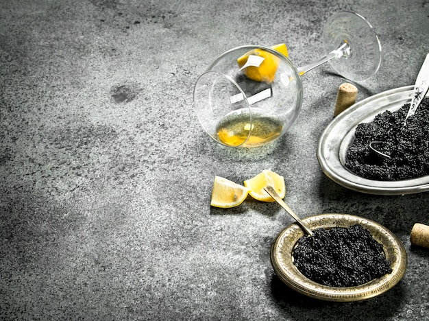 Black caviar with a glass of white wine. on rustic background .