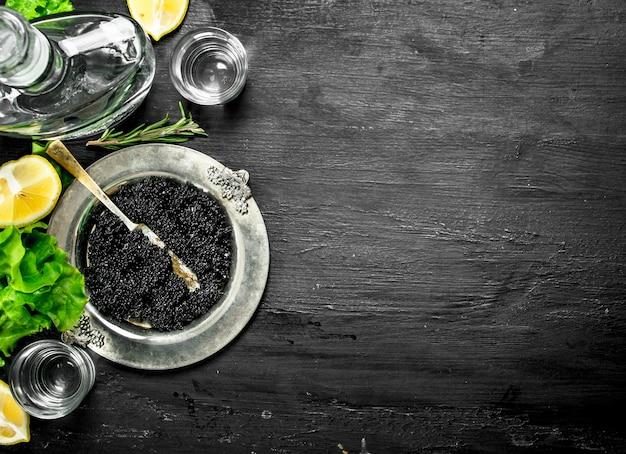 Черная икра с водкой и дольками лимона. на черной доске.