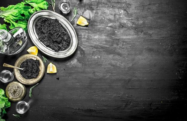 Черная икра с водкой и дольками лимона.