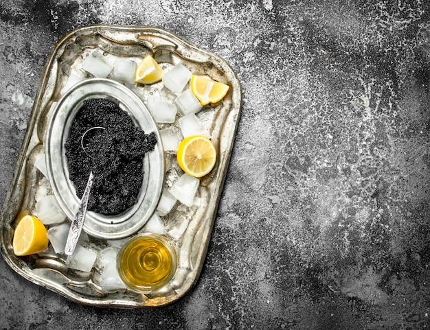 화이트 와인과 시골 풍 테이블에 레몬 조각 블랙 캐 비어.