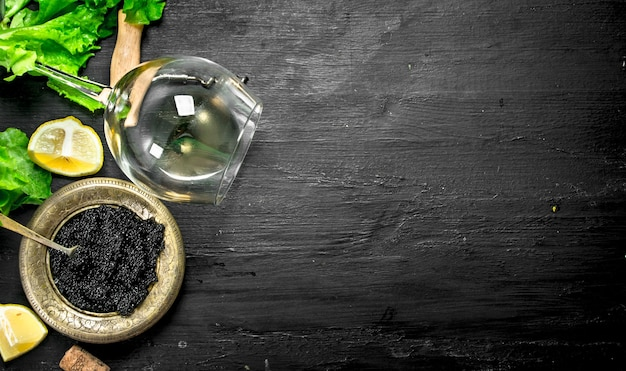 Black caviar with white wine and herbs. on a black chalkboard.