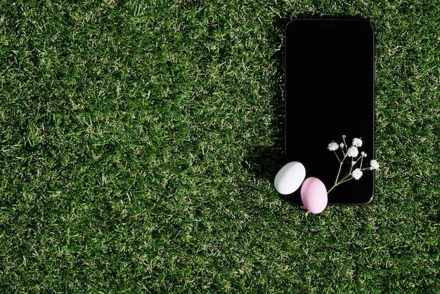 緑の草の上にチョコレートで艶をかけられたイースターエッグで飾られた黒い携帯電話。ハッピーイースターのコンセプト。スペースをコピーします。上面図