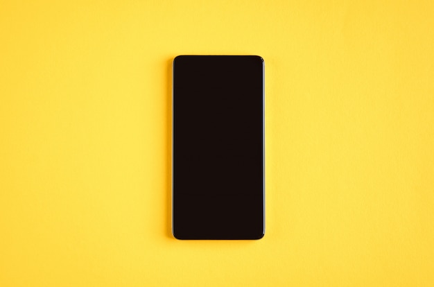 Black cellphone on yellow surface, mobile phone.