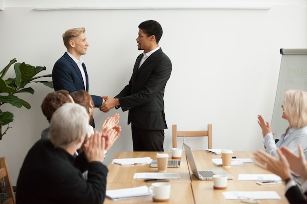 Black ceo and white businessman shaking hands at group meeting