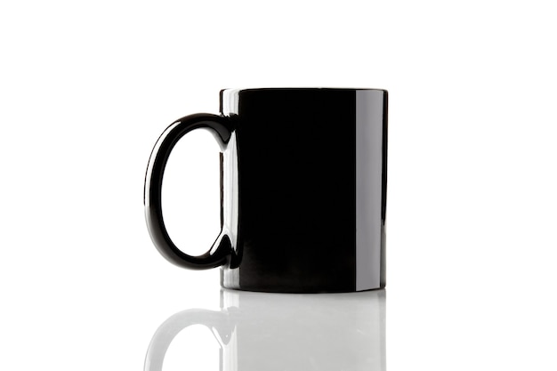 Black ceramic cup for coffee or tea on glossy surface isolated on white