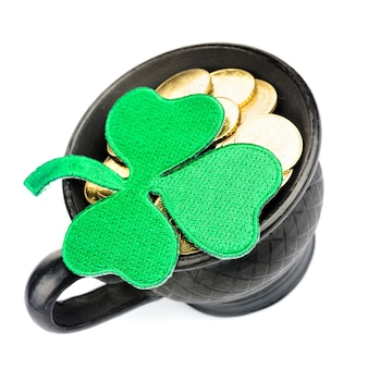 Black ceramic pot with golden coins and shamrock isolated on white. st. patrick day concept