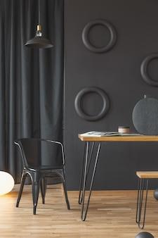 Черный стул рядом с деревянным столом у стены с кругами в темном интерьере домашнего офиса