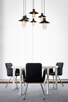 Black chair and table in modern office room interior with ceiling lamps