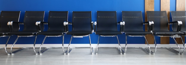 Black chairs on row on blue wall modern office