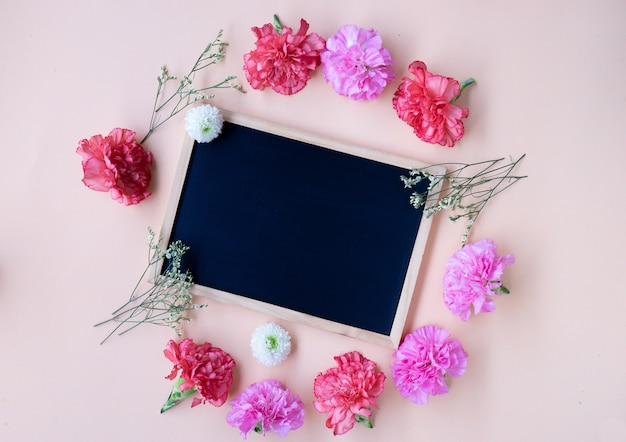 Black chalk board with fresh carnation flower on soft cream background with copy space