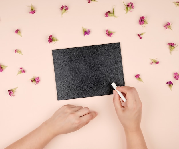 Black chalk frame and two female hands with piece of white chalk