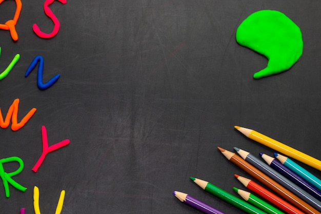 Black chalkboard with colorful pencils and letters, concept for education