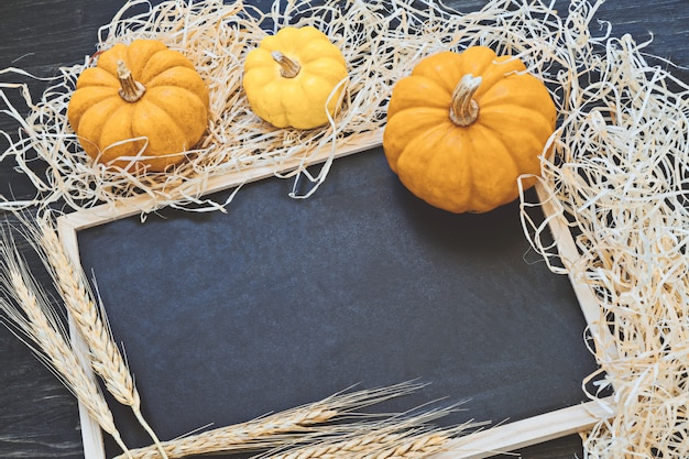 Black chalkboard with copy space and decorative yellow pumpkins