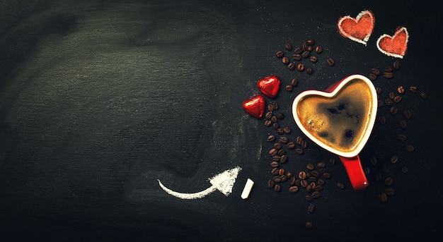 Black chalkboard with a heart shaped cup of coffee