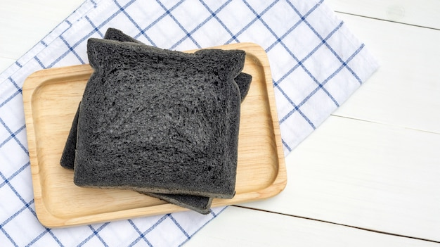 Black charcoal bread on a white wooden table.