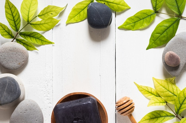 A black charcoal soap on white background with green leaf and rock for spa concept