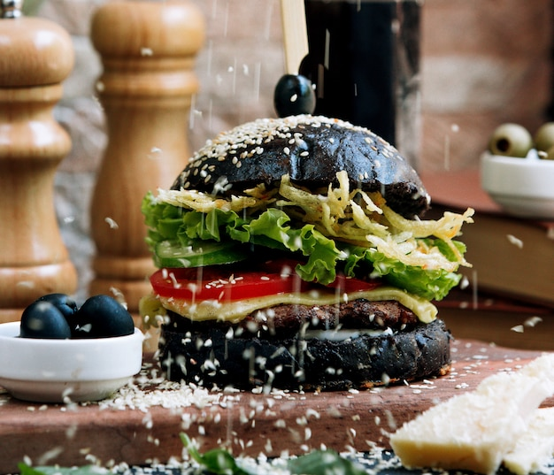 Black cheeseburger topped with sesame seeds
