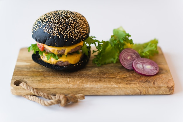 Black cheeseburger on wooden chopping board, grey background.