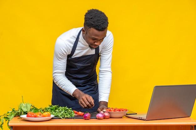 黒人シェフがラップトップで何かを調理して見たり、オンラインでレシピを閲覧したりする