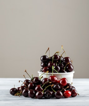 Black cherries in a bowl on grungy and grey gradient surface. side view.