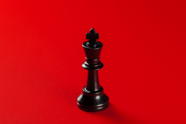Black chess king piece on red background