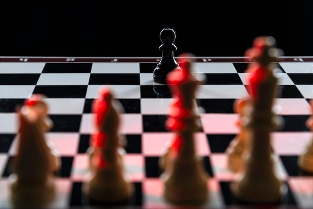 Black chess pawn against an army of white chess pieces on a chessboard