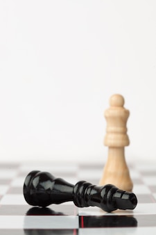 Black chess piece lying while white standing