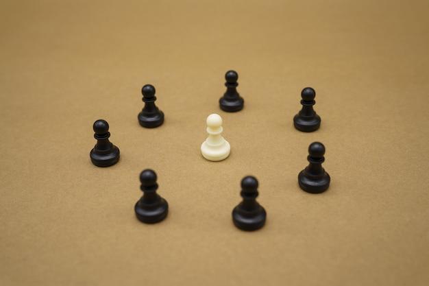 블랙 체스 조각과 갈색 표면에 하나의 흰색 폰
