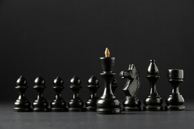 Black chess pieces on black background