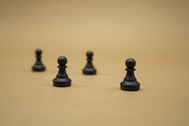 Black chess pieces on brown surface