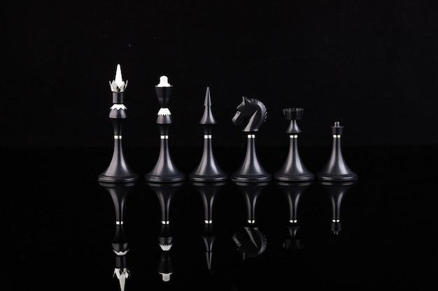 Черные шахматные фигуры на отражающей поверхности. бизнес-концепция. игра, стратегия, мудрость, решительность.