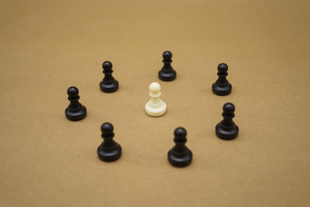 Black chess pieces and one white pawn on brown surface
