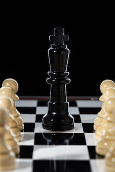 Black chess queen and army of white pawns on a chessboard