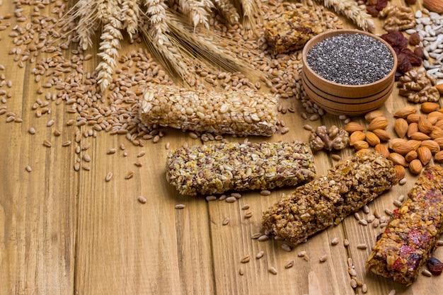 ブラックチアシード、シリアルグラノーラバー、ナッツ。健康的な食事の菜食主義の食糧。上面図。木の表面
