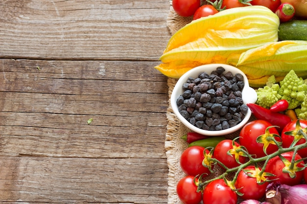 Black chickpea in a bowl with raw vegetables on a wooden table close up with copy space