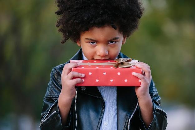 빨간색 선물을 가진 흑인 아이입니다. 공원 배경에서. 어린이 크리스마스 개념.